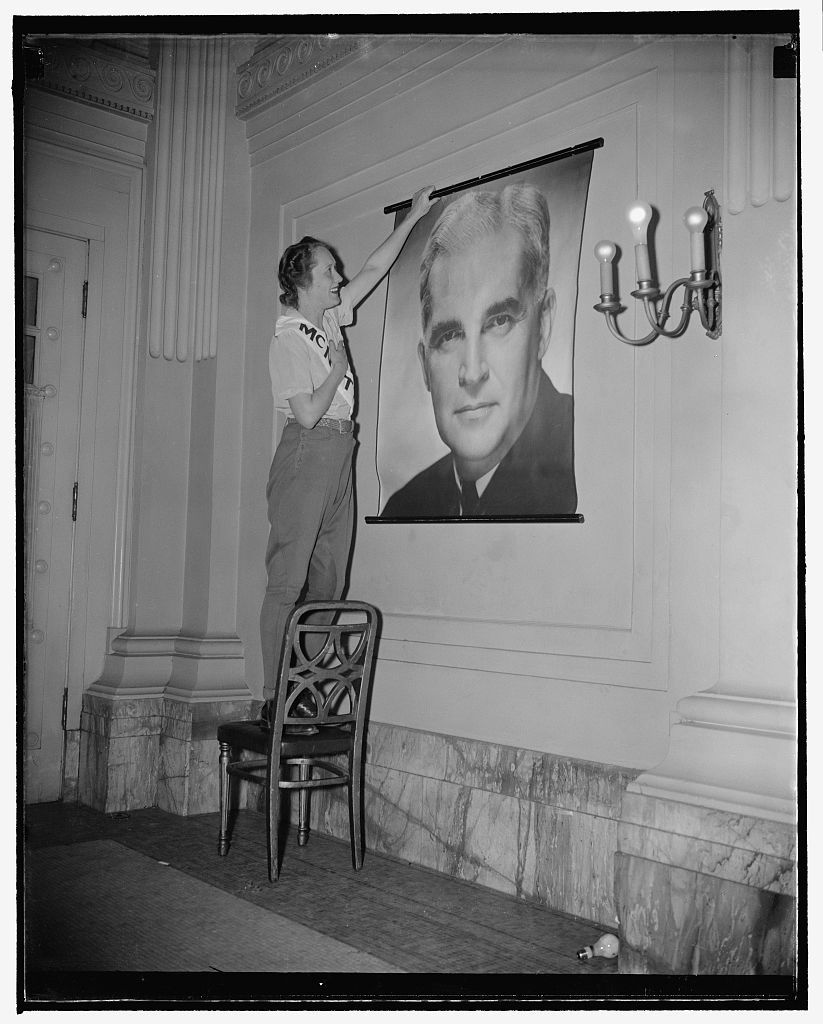 A woman named Mrs. O'Gridley, hanging up a photograph of handsome Paul, circa 1939-1940. This image became synonymous with McNutt's presidential campaign literature. Image courtesy of the Library of Congress.